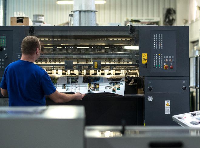 Pracownik przy maszynie wykonuje druk offsetowy w Gdańsku w firmie Drukarnia Misiuro